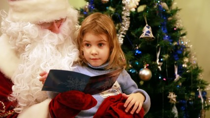 Girl sitting in Santa Claus kneeling in front of tree