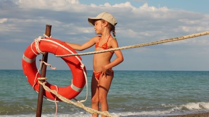 Girl puts a rope and poses next to lifebuoy ring