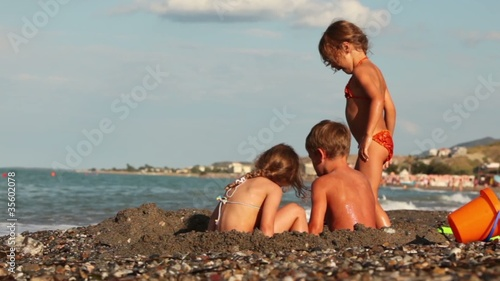 Three children dig pit in sand before sea water