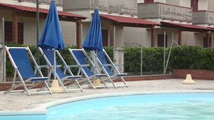 Several deckchairs facing the pool against backdrop of an hotel