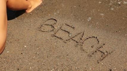 word beach is written on sand, sea wave appear