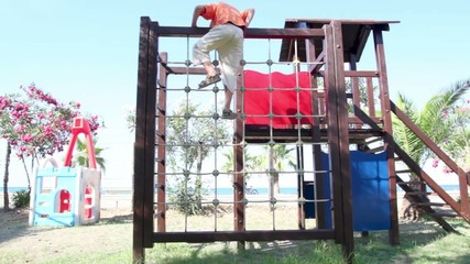 Two kids on playground, climbing on the obstacle
