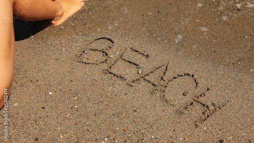word beach is written on sand, sea wave appear