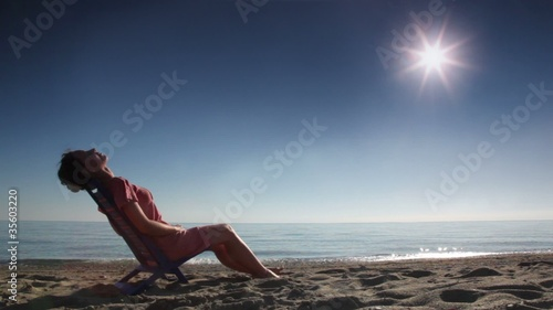 Woman sitting on deckchair and tans
