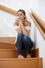 Sad girl sitting on stairs at home