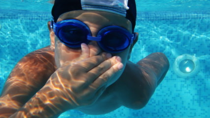 Boy in glasses for swimming dives into pool and swims