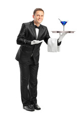 Butler with bow tie carrying a tray with a cocktail on it