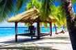 Tropical gazebo with chairs on a beach with palm trees