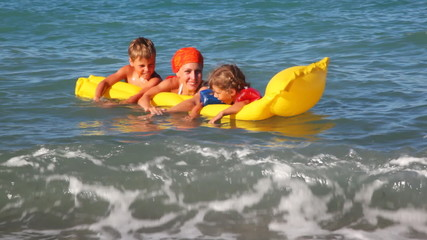 Mother with two kids swim in wavy sea