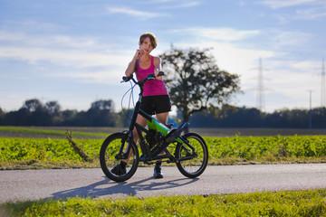 sportliche Frau mit Streetstepper auf Radweg