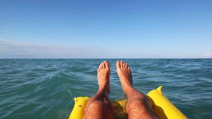 Legs of man swim on sea surface with mattress