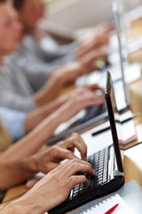 Viele Hände an Laptops