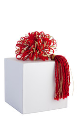 Rich red and gold ribbon with tassel on gift box.