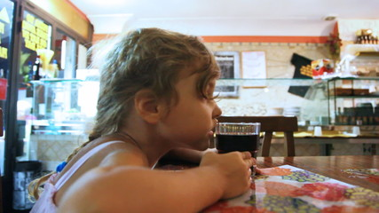 Little girl sits at table and drink from glasses