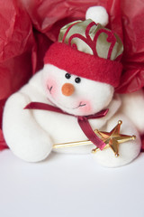Smiling snowman on gift box with red tissue paper.