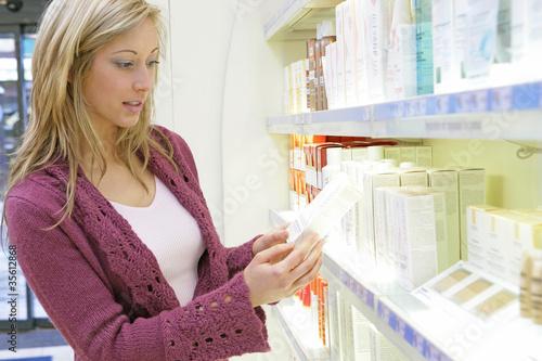 Femme lisant la composition des cosmétiques