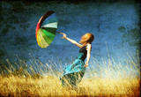 Fototapety Redhead girl with umbrella at windy grass meadow.