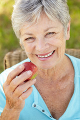 Senior woman eating apple