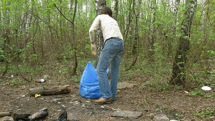Man collects trash to garbage bag in forest