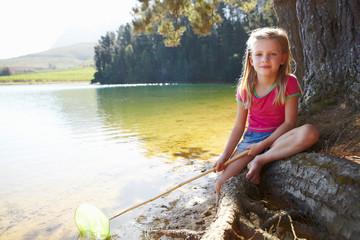Happy girl fishing at lake