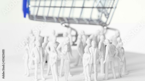 Little toy men and women stand in front of big shopping trolley