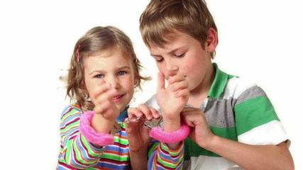 Two children plays with furry handcuffs