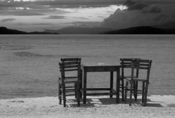Empty wooden table and chairs on seafront