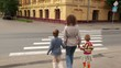 Mother and kids goes by pedestrian crossing road