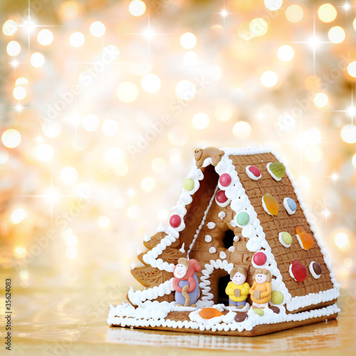 Christmas gingerbread house decoration on defocused lights backg