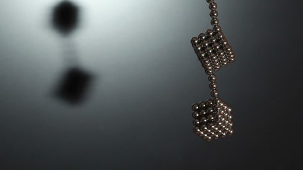Two cubes compound of magnet spheres hangs on chain