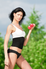 Woman doing exercise with dumbbell
