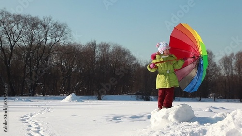 Girl stand on snow height and hold umbrella