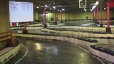 Carting race is in indoor place with video board