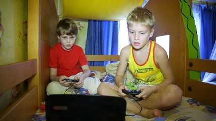 Two boys sit and play a computer game