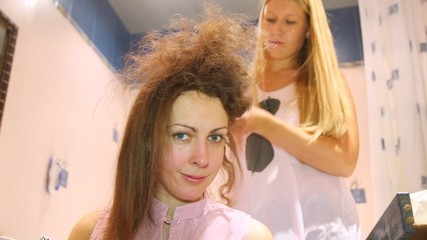 The hairdresser does a hairdress to young woman