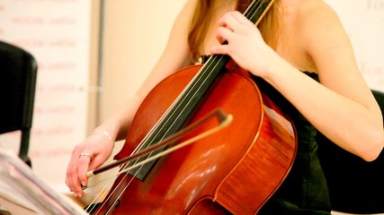 Close-up of woman plays a violoncello
