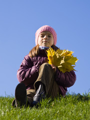 girl  with autumnal leaves against sky