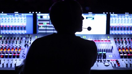 Silhouette of sound producer, which sits at mixer panel