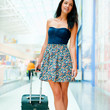 Portrait of young woman walking inside modern international airp
