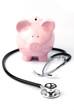 Leinwandbild Motiv Piggy bank and stethoscope isolated on white