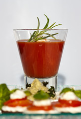 Tomato soup in a glass with fresh rosemary