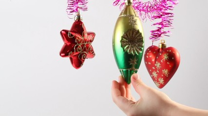 Christmas-tree decoration swing on tinsel, hand touches it