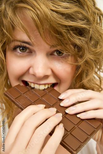 Blonde Frau genießt lachend eine Tafel Schokolade.