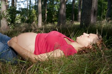 schwangere junge frau entspannt sich im wald