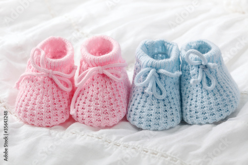 Blue and pink baby booties on white background