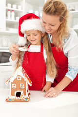 Happy woman and little girl making gingerbread house