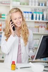 lächelnde apothekerin mit telefon am computer