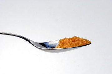 steel spoon filled with bown sugar