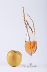A glass filled with orange substance, spice and an apple