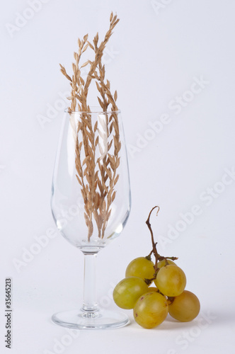 A glass filled with spice and a bunch of grapes #1